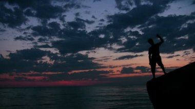 Youngster stands on rock against sunset sky and sea — Stock Video