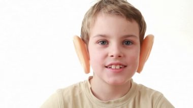 Boy with big plastic ears, sitting on a white background, turns his head — Video Stock