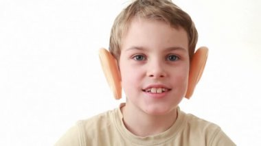 Boy with big plastic ears, sitting on a white background, turns his head — Stock Video