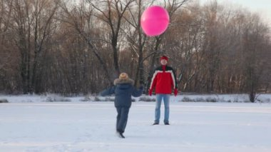 Father and son plays with air-balloon in snowfield — Stock Video