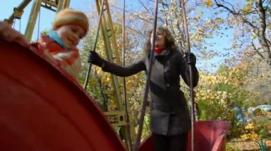 Woman and boy teetering on swing boat — Stock Video