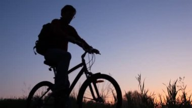 Silhouette of man on bicycle stands in field and looks at sky — Stock Video