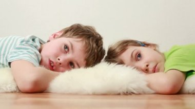 Boy and little girl lie on floor on shaggy carpet — Video Stock
