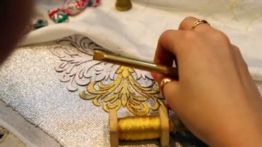 Female hand embroider with gold thread and lace needle on fabric — Stock Video