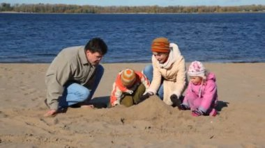 Family constructing sand buildings on beach — Stock Video
