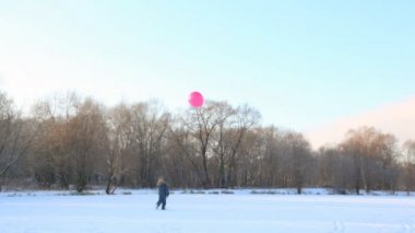 Boy plays with air-balloon in snowfield — Stock Video