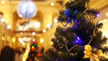 Close up New Year's tree with blinking dark blue garlands in shopping centre — Stock Video