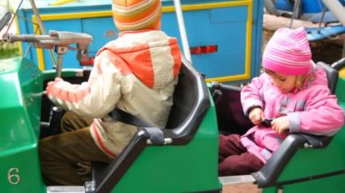 Boy and girl sits in dodgem in city park amusement — Stock Video