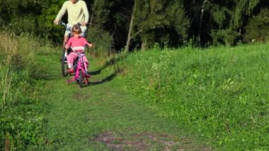 Man and girl riding bicycles in park — Video Stock