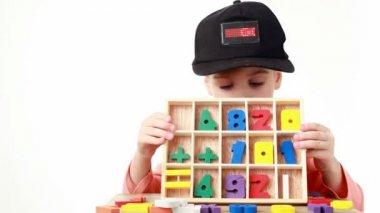 Meisje in cap met led display doos met cellen met houten figuren — Stockvideo