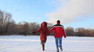 Man and woman runs in snowfield — Stock Video
