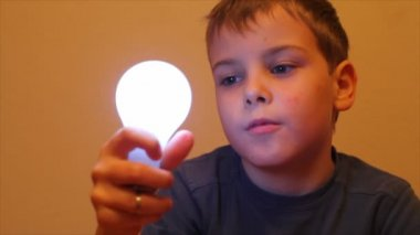 Boy in blue T-shirt switchs on and off a light bulb — Stock Video