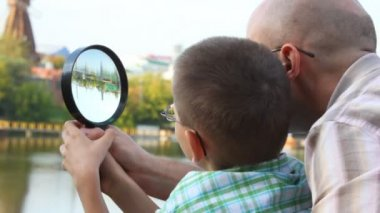 Father and son standing on bank of river and looks through magnifying glass — Stock Video