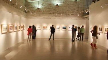 группа молодых людей смотрит на фотографии в выставочном зале — Стоковое видео