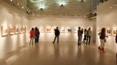 Grupa młodych ludzi patrzy na zdjęcia w hali wystawowej — Wideo stockowe