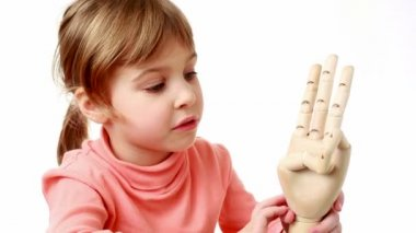 Girl flexes fingers of wooden model of human hand and brings it closer to screen — Stock Video