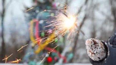 查尔兹拉着燃烧的烟火反对棵圣诞树 — 图库视频影像