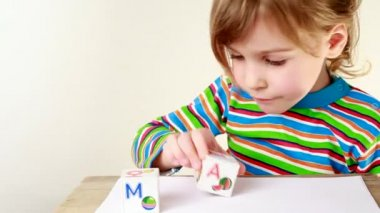 Girl in multicolor striped T-shirt puts together cubes with letters for obtaining word Mama — Stock Video