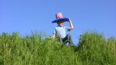 Boy in american flag hat sits on grass and holds globe — Stock Video