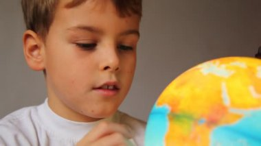 Boy looks at shone globe and rotates it indoors close up — Stock Video