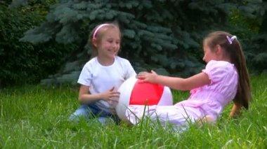 Flickor sitter med boll på gräset i parken och spelar — Stockvideo