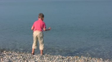 Boy stands on pebble beach and throws stones — Stock Video
