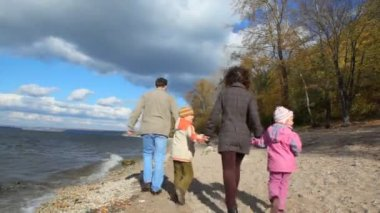 Family walking on sandy bank of river — Stok video