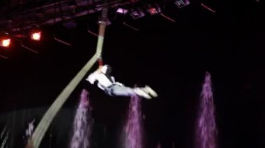 Agile acrobat rapidly spins on tethers in an air in circus — Stock Video