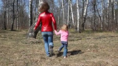 Happy mother and little daughter having joined hands runs round the birch — Stock Video