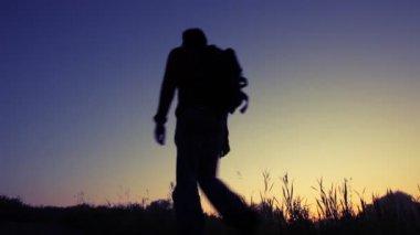 силуэт человека идет в гору против неба — Стоковое видео