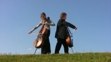 Man and woman plays violoncellos on hill — Stock Video