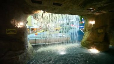 Through a waterfall of stone cave seen bathing in pool in waterpark — Stock Video