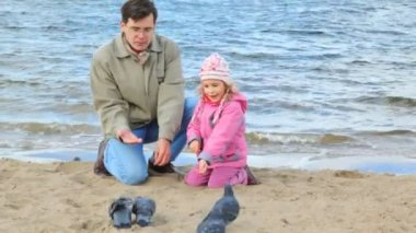 Man and girl sits on beach and feeds pigeons — Vidéo