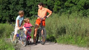 Family of three with bicycles in field — Stockvideo