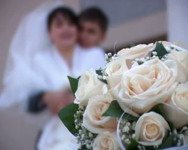 Focusing from wedding bouquet to kissing groom and bride — Stock Video