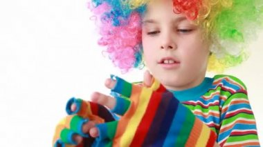 Boy in a ridiculous multicolor wig wears gaudy striped gloves — Stock Video
