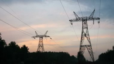 The sky darkens over transmission equipment and forest — Stock Video