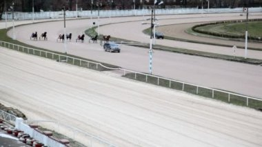 Review of horses with equestrians competing on hippodrome track before an car — Stock Video