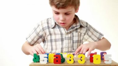 Boy raises box with cells containing figures and shows equation — Stock Video