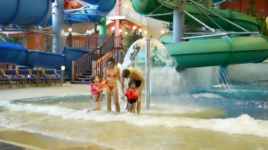Charming woman , man and children fool near fountain in pool in water park — Stock Video