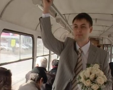 Groom with wedding bouquet stands in bus and holds the handrail — Stock Video