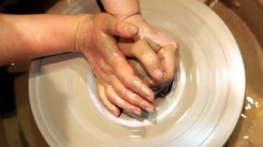 Hands mould pot rotating on potters wheel and moisten with its sponge — Stock Video