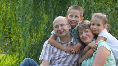 Lachen en gelukkige familie van vier personen zit op groen gras in park — Stockvideo
