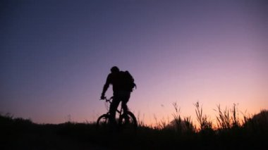 Bicyclist rides uphill against sunset sky — Stock Video