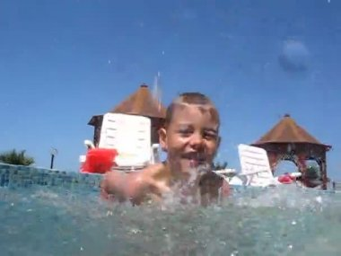Boy in swimming pool splashes water to camera — Stock Video