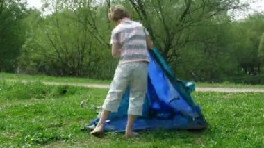 The boy establishes tent on a glade in summer day. Time lapse. — Stock Video