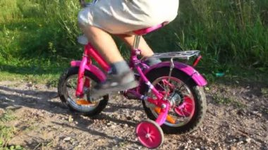Fahren mit dem fahrrad im park, junge mädchen drückt ihn — Stockvideo