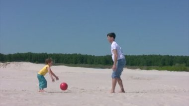 Man and boy plays with ball on beach — Stockvideo