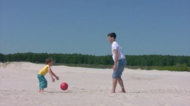 Man and boy plays with ball on beach — ストックビデオ