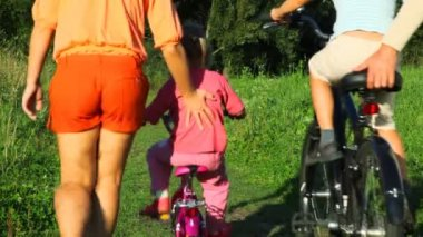 Parents helps a kids riding bicycles from camera in park — Stock Video